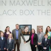 Another photo of the family posing in front of the photo of Linn Maxwell Keller.